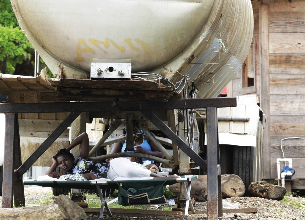 Women and children rest under a water tank at a migrant camp in Lajas Blancas, Darien province, Panama, Saturday, Aug. 29, 2020. The flow of migrants ...