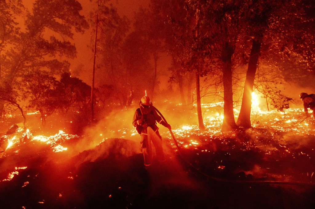 A firefighter battles the Creek Fire as it threatens homes in the Cascadel Woods neighborhood of Madera County, Calif., on Monday, Sept. 7, 2020. (AP ...