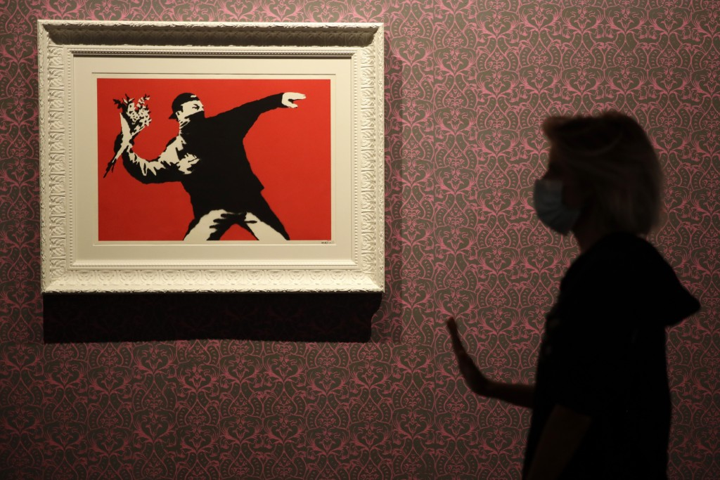 "A worker walks past ""Love Is in the Air"", a screen print on paper, by British artist Banksy, a day before the unveiling of an exhibition in Rome, Mond..."