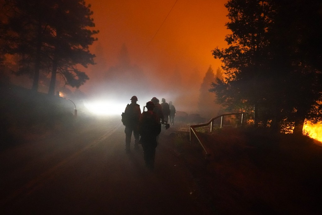 Members of the Laguna Hotshots, out of the Cleveland National Forest, walk on a road while fighting the Creek Fire, Sunday, Sept. 6, 2020, in Big Cree...