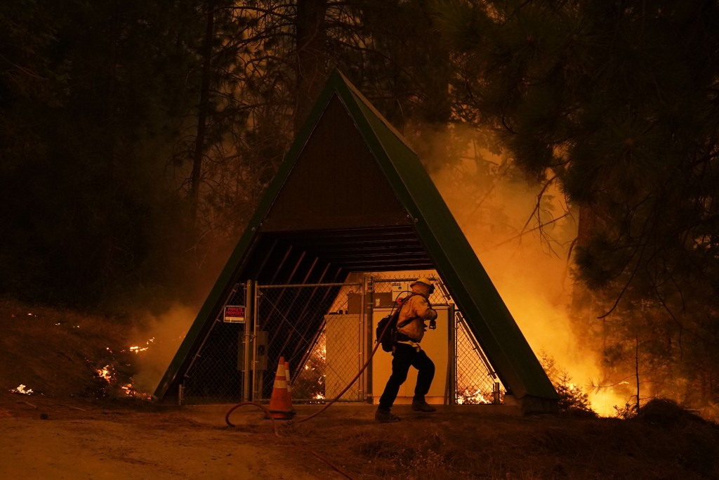 A firefighter runs with a hose in front of a structure while fighting the Creek Fire, Sunday, Sept. 6, 2020, in Shaver Lake, Calif. (AP Photo/Marcio J...