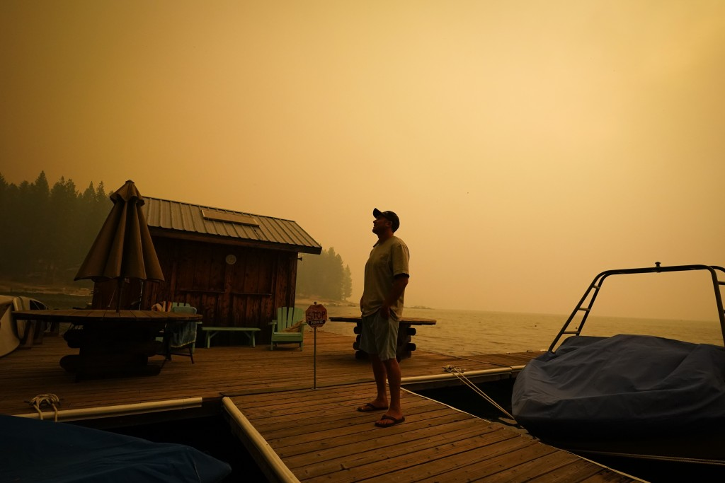 A business owner, who declined to give his name, looks up at the smoke-covered sky from the Creek Fire at his boat rental place Sunday, Sept. 6, 2020,...