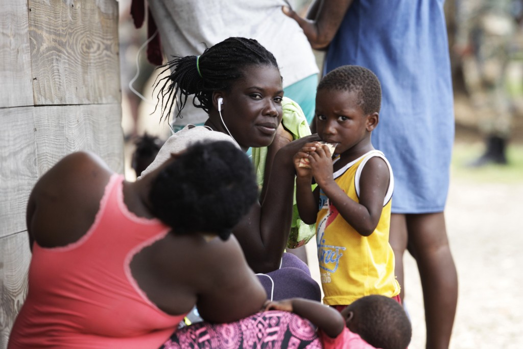 Women and children sit idle at a migrant camp amid the new coronavirus pandemic in Lajas Blancas, Darien province, Panama, Saturday, Aug. 29, 2020. In...