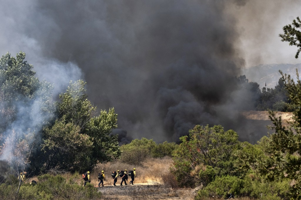 Los Angeles Fire Department firefighters hike into the Sepulveda Basin to fight a brush fire in the Sherman Oaks area of Los Angeles, Sunday, Sept. 6,...