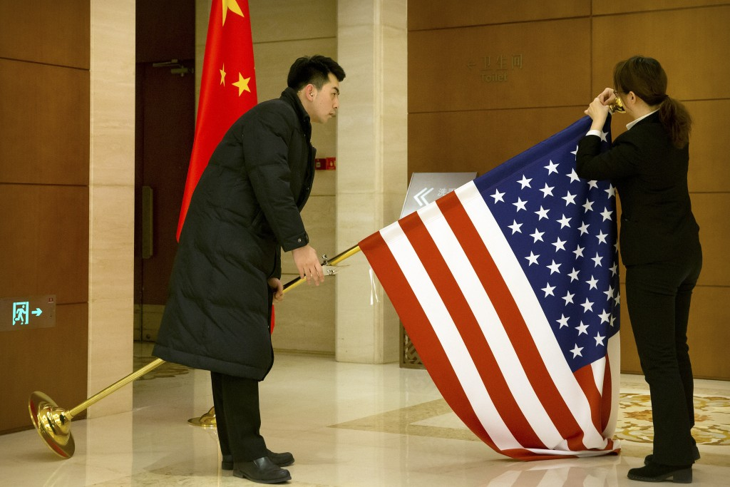 FILE - In this Feb. 14, 2019, file photo, Chinese staffers adjust a U.S. flag before the opening session of trade negotiations between U.S. and Chines...