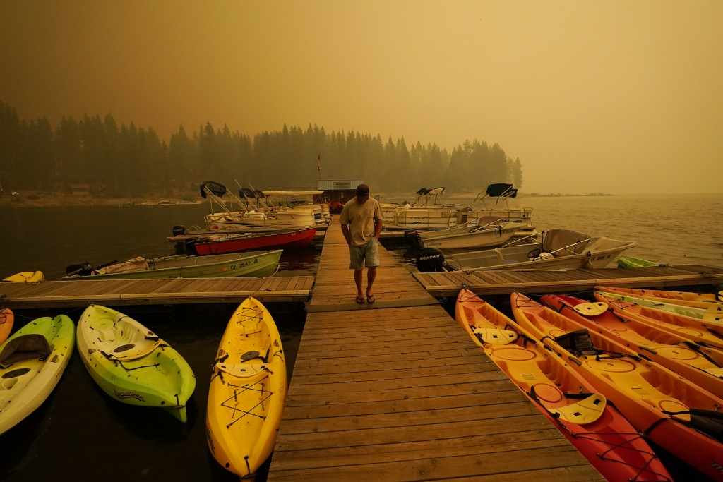 A business owner, who declined to give his name, walks next to kayaks he rents as smoke from the Creek Fire fills the sky, Sunday, Sept. 6, 2020, in S...