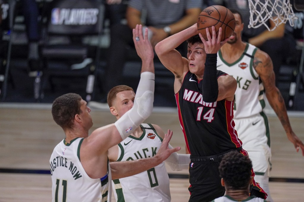 Miami Heat's Tyler Herro looks to pass past Milwaukee Bucks' Brook Lopez (11) and Donte DiVincenzo during the first half of an NBA conference semifina...