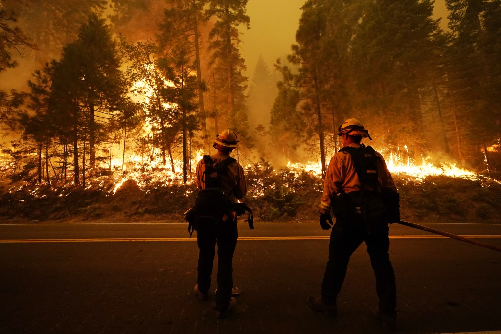 Firefighters keep an eye on the Creek Fire along state Highway 168, Sunday, Sept. 6, 2020, in Shaver Lake, Calif. (AP Photo/Marcio Jose Sanchez)