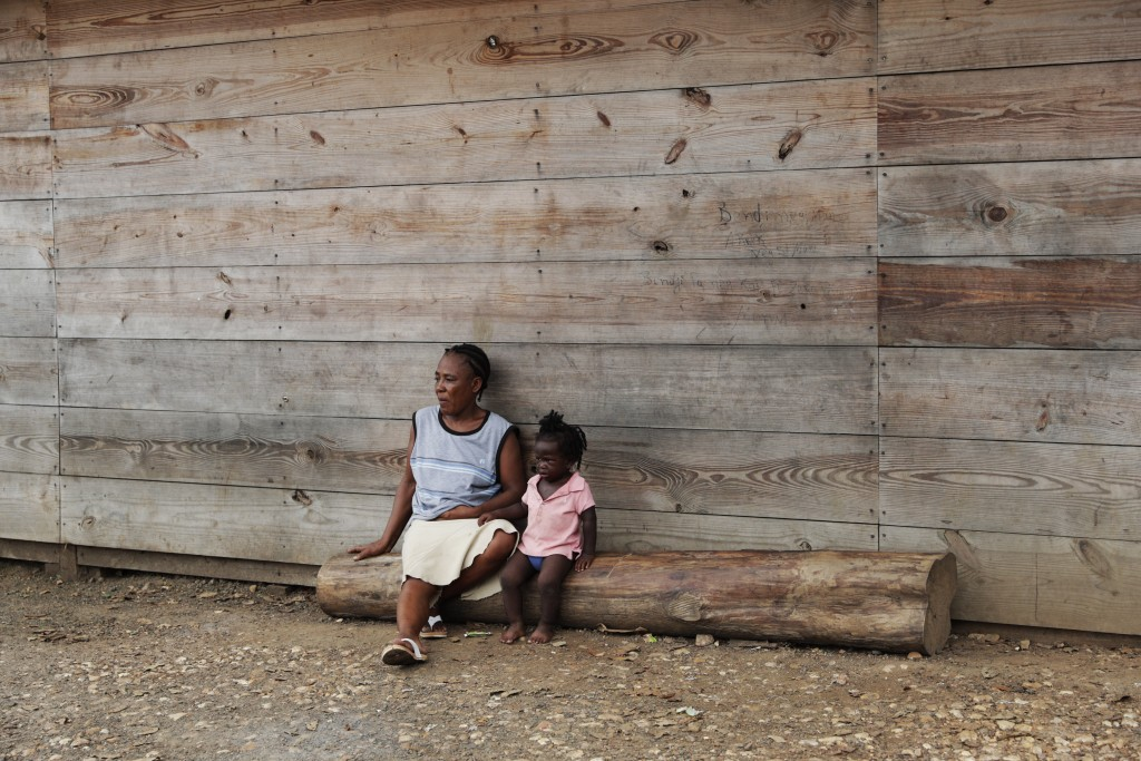 Duperat Laurette sits on a log with a girl at the entrance of a migrant shelter in Lajas Blancas, Darien province, Panama, Saturday, Aug. 29, 2020. Th...