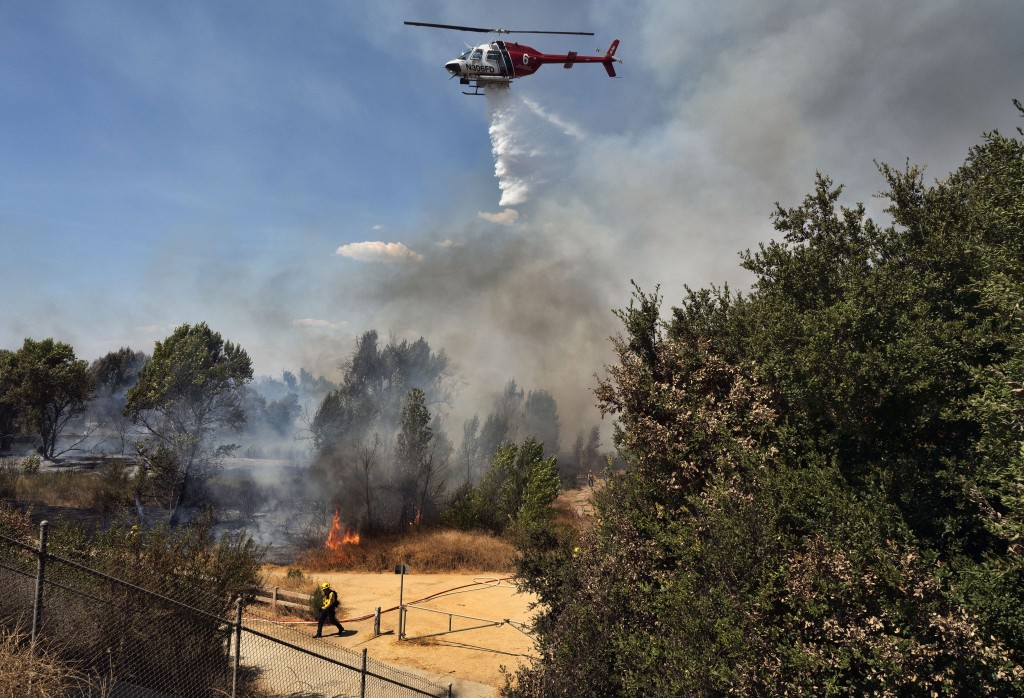 A Los Angeles Fire Department helicopter makes a water drop over a brush fire in the Sepulveda Basin in the Sherman Oaks area of Los Angeles, Sunday, ...