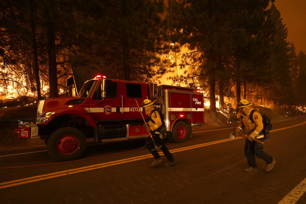 Firefighters run along state Highway 168 while fighting the Creek Fire, Sunday, Sept. 6, 2020, in Shaver Lake, Calif. (AP Photo/Marcio Jose Sanchez)