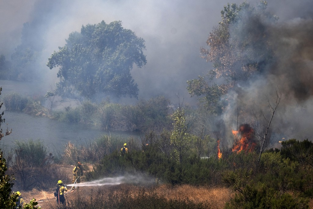 Los Angeles Fire Department personnel work to douse several small brush fires in the Sepulveda Basin in the Sherman Oaks area of Los Angeles, Sunday, ...