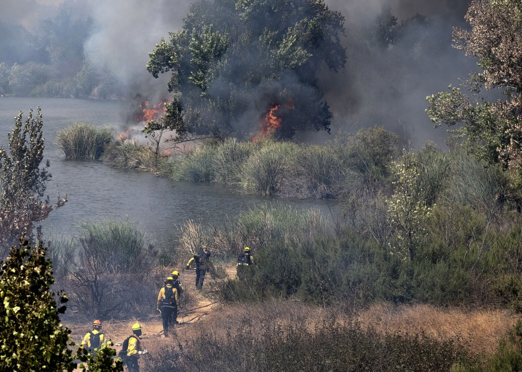 Los Angeles Fire Department firefighters make their way into the Sepulveda Basin to fight a brush fire in the Sherman Oaks area of Los Angeles, Sunday...