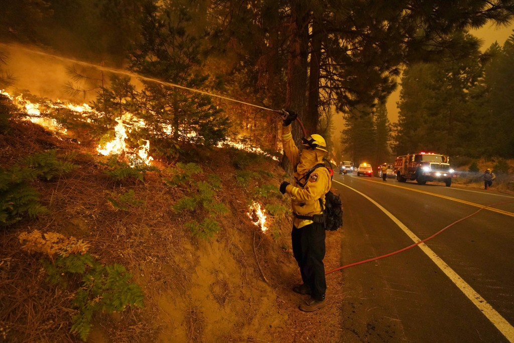 A firefighter uses a hose while fighting the Creek Fire along state Highway 168, Sunday, Sept. 6, 2020, in Shaver Lake, Calif. (AP Photo/Marcio Jose S...