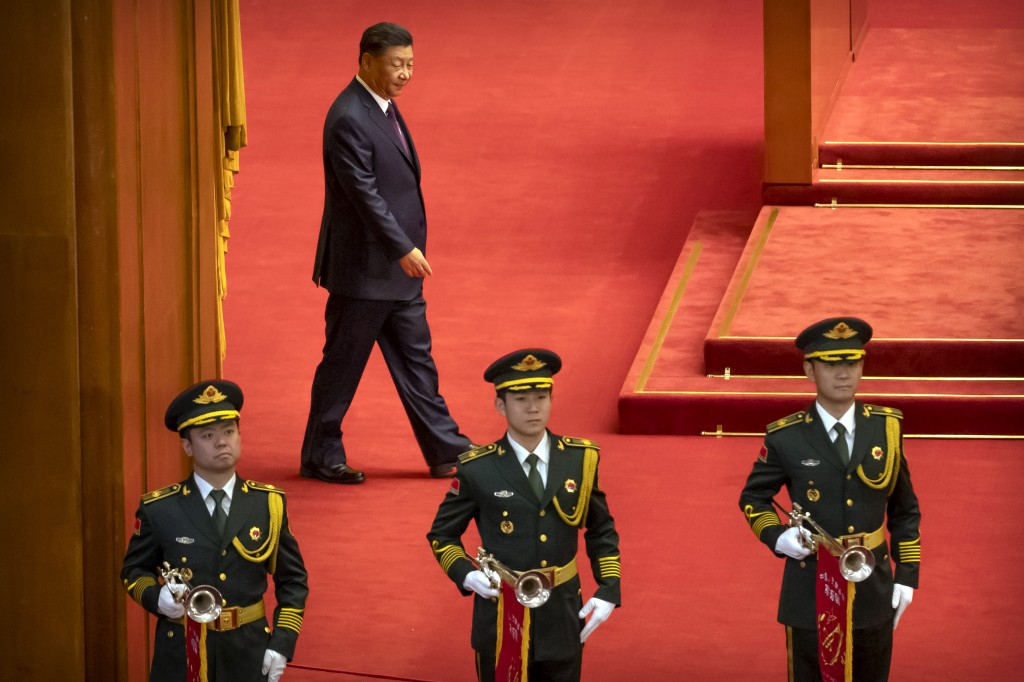 Chinese President Xi Jinping, rear, arrives for an event to honor some of those involved in China's fight against COVID-19 at the Great Hall of the Pe...