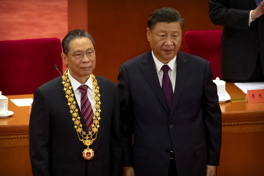 Chinese President Xi Jinping, right, stands with Chinese medical expert Zhong Nanshan after awarding him a medal at an event to honor some of those in...