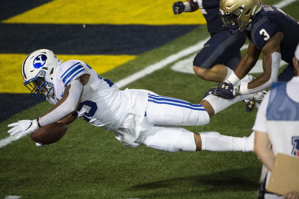 BYU running back Tyler Allgeier dives for a touchdown as Navy defensive back Cameron Kinley (3) defends during the second half of an NCAA college foot...