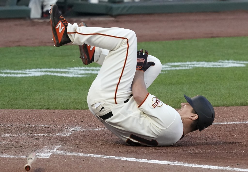 San Francisco Giants' Alex Dickerson reacts after getting hit by a ball that bounced off his bat during the fifth inning of a baseball game against th...