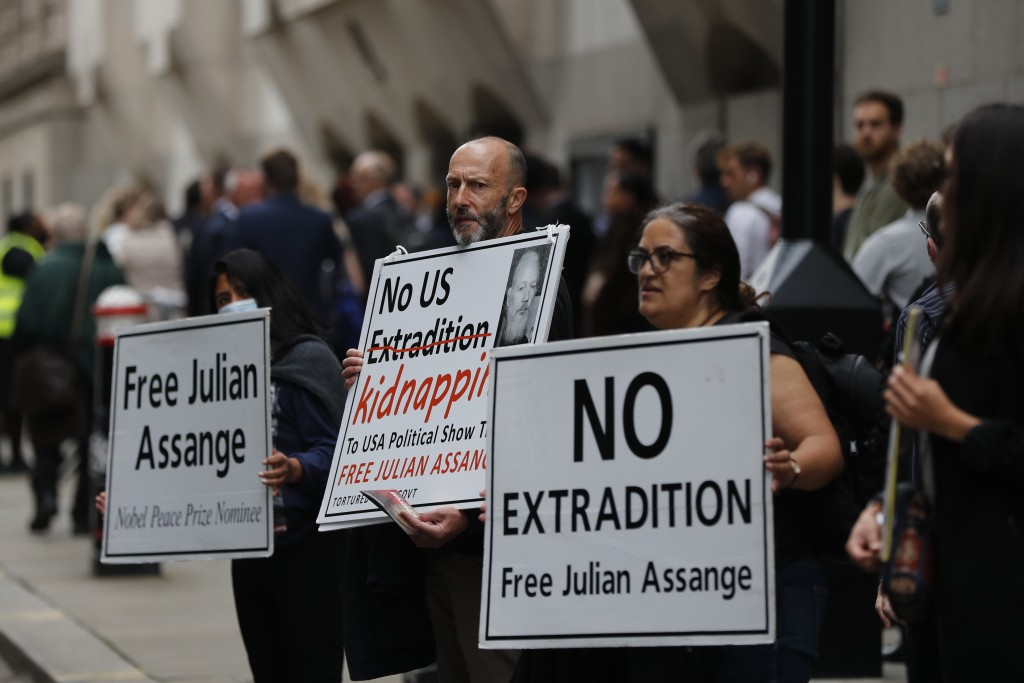 Demonstrators hold placards near the Central Criminal Court Old Bailey in London, Tuesday, Sept. 8, 2020. Lawyers for WikiLeaks founder Julian Assange...