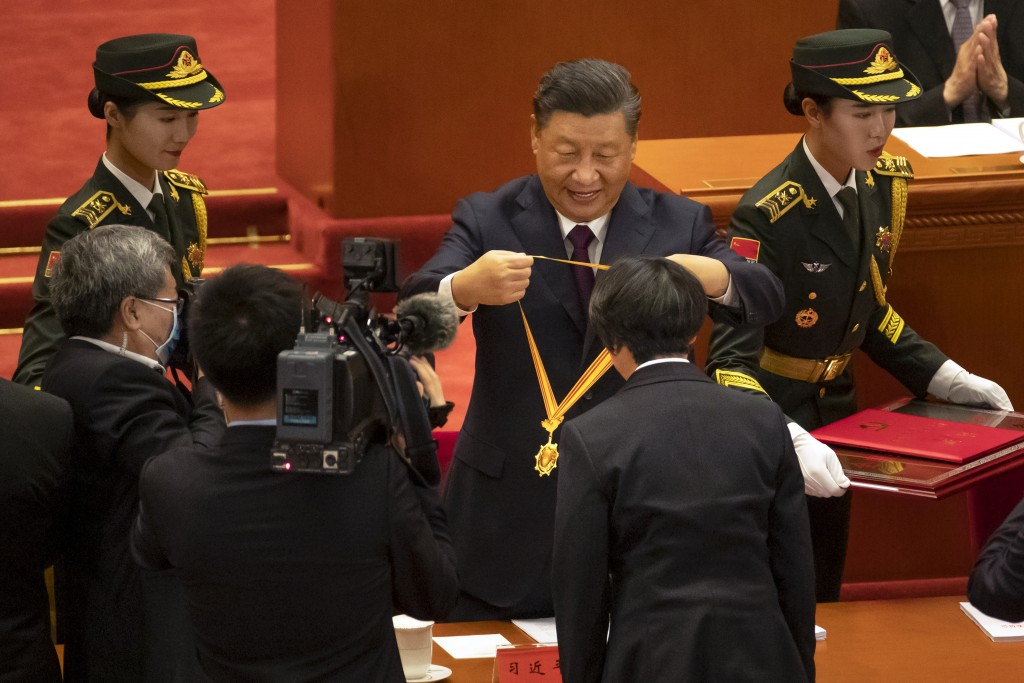 Chinese President Xi Jinping, rear center, presents a medal to an honoree at an event to honor some of those involved in China's fight against COVID-1...