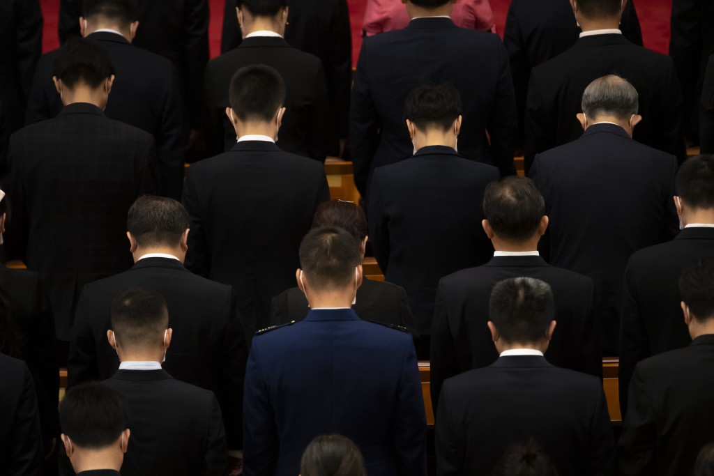 Attendees bow their heads during a momet of silence at an event to honor some of those involved in China's fight against COVID-19 at the Great Hall of...