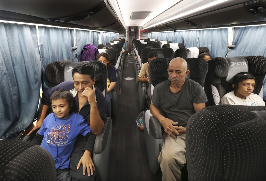 FILE - In this July 18, 2019 file photo, migrants sit in a bus that was organized by the Mexican government, which will take them from an immigration ...