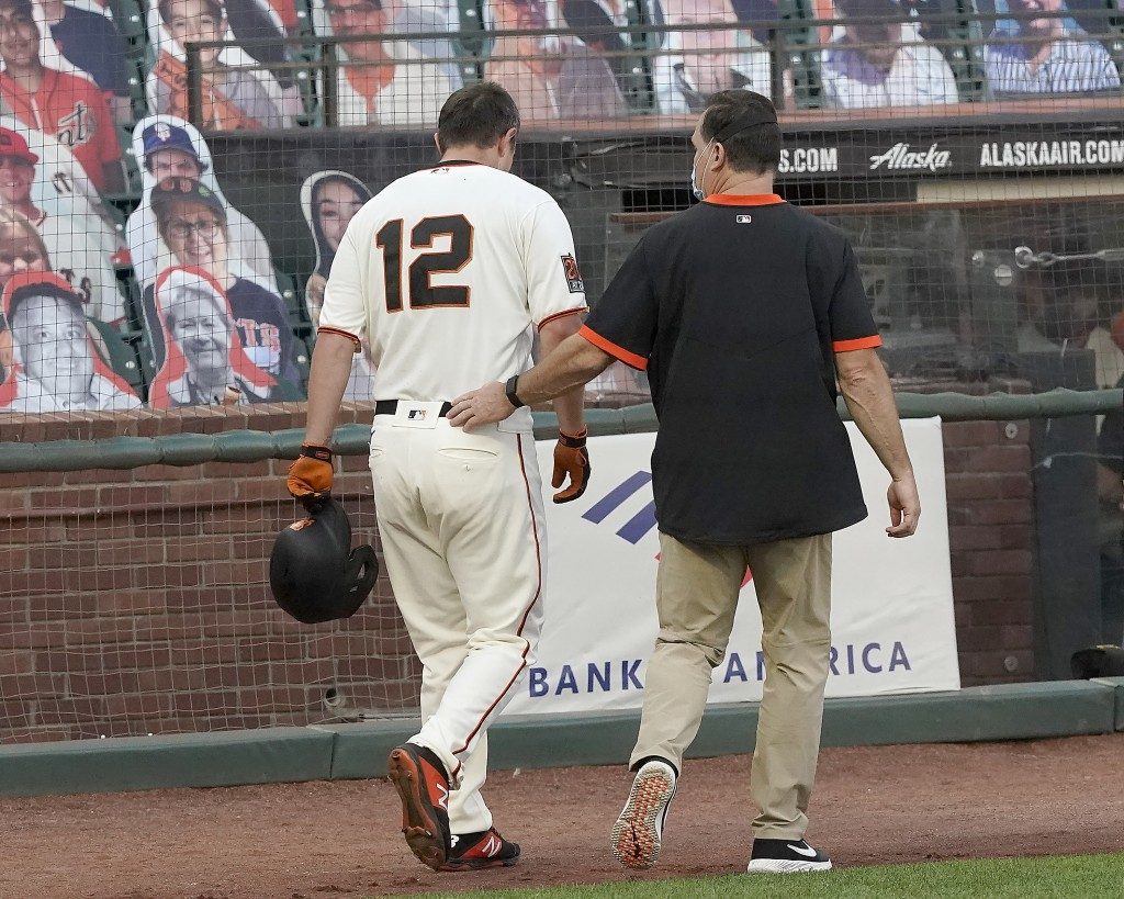 San Francisco Giants' Alex Dickerson (12) walks off the field with the team trainer after getting hit by a ball that bounced off his bat during the fi...