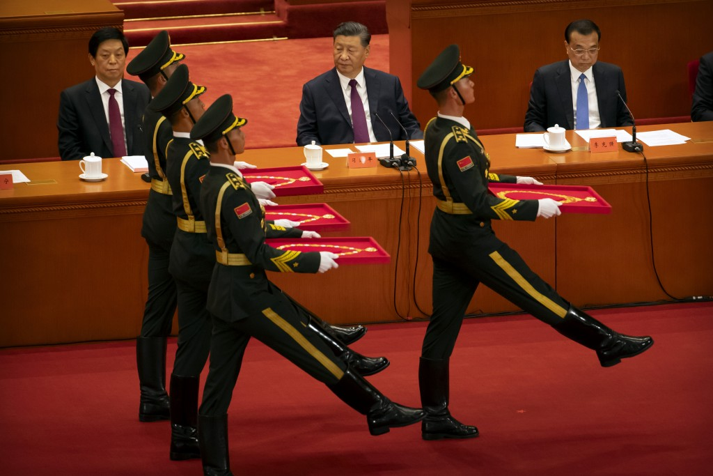 Chinese President Xi Jinping, center, watches as an honor guard carrying medals marches at an event to honor some of those involved in China's fight a...