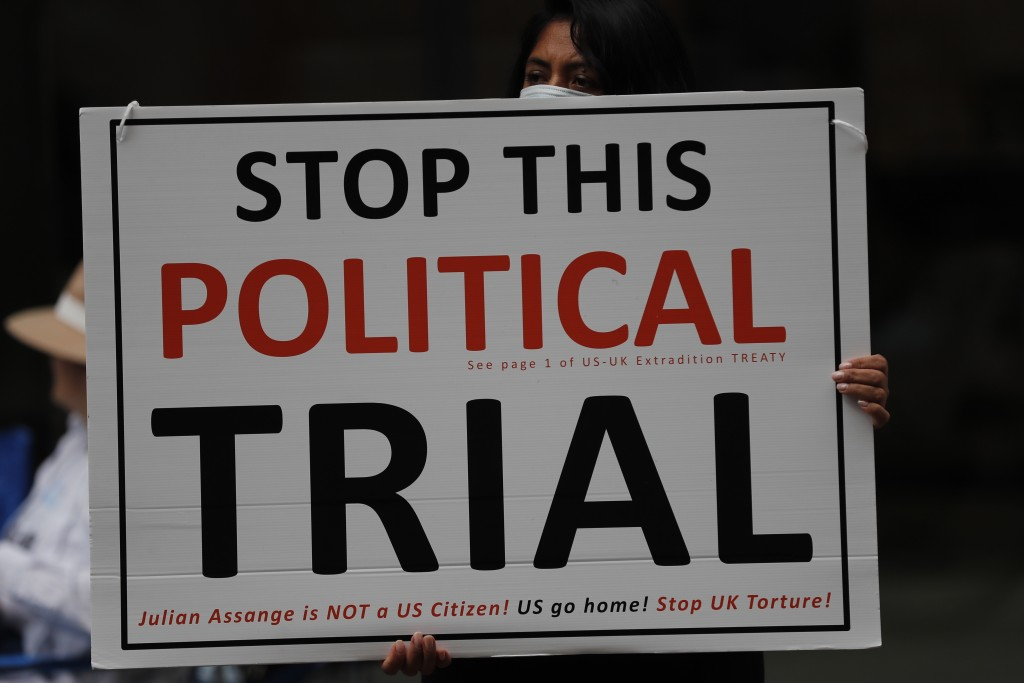 A demonstrator hold a placard near the Central Criminal Court Old Bailey in London, Tuesday, Sept. 8, 2020. Lawyers for WikiLeaks founder Julian Assan...