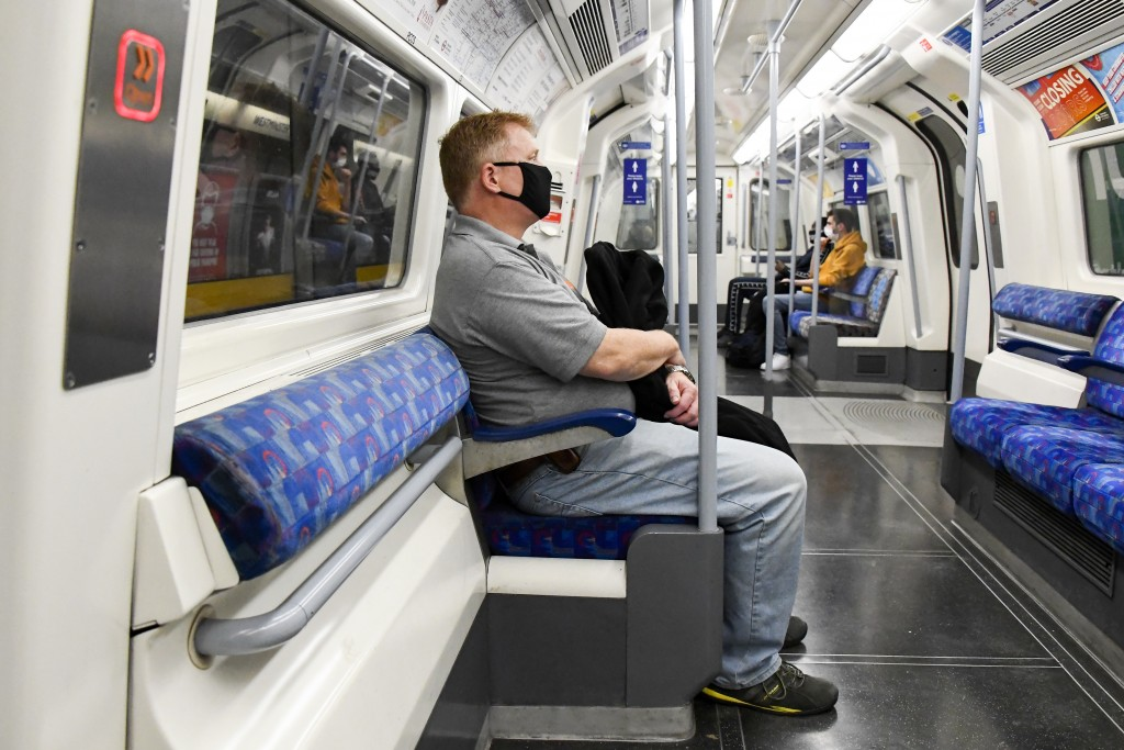 A man wears a face mask to protect against infection from coronavirus as he sits on an Underground train, in London, Tuesday, Sept. 8, 2020. (AP Photo...