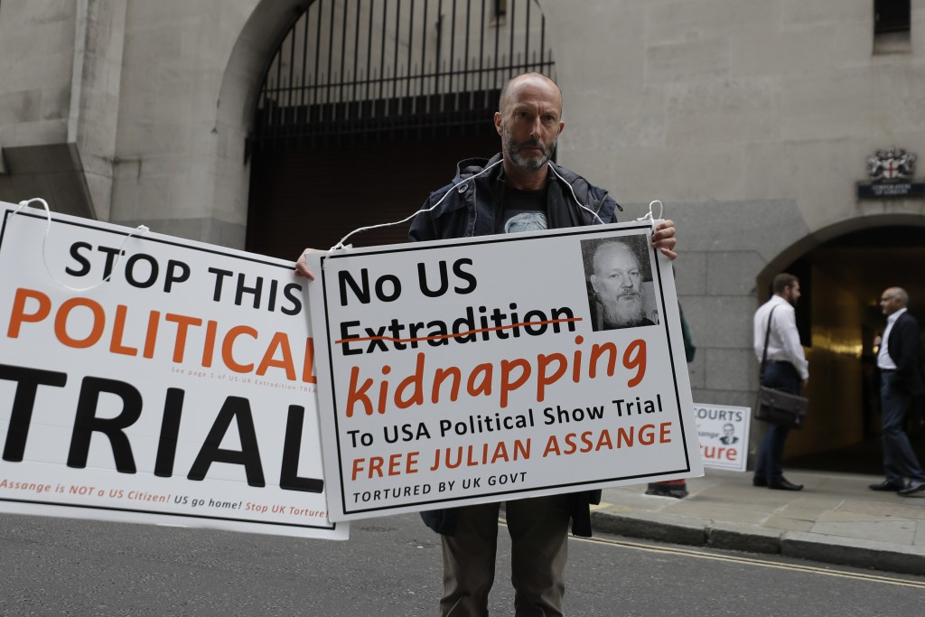 A demonstrator holds placards near the Central Criminal Court Old Bailey in London, Tuesday, Sept. 8, 2020. Lawyers for WikiLeaks founder Julian Assan...
