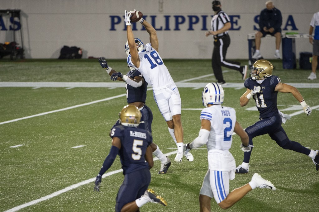 BYU wide receiver Gunner Romney (18) leaps to catch a pass over Navy defensive back Cameron Kinley during the second half of an NCAA college football ...