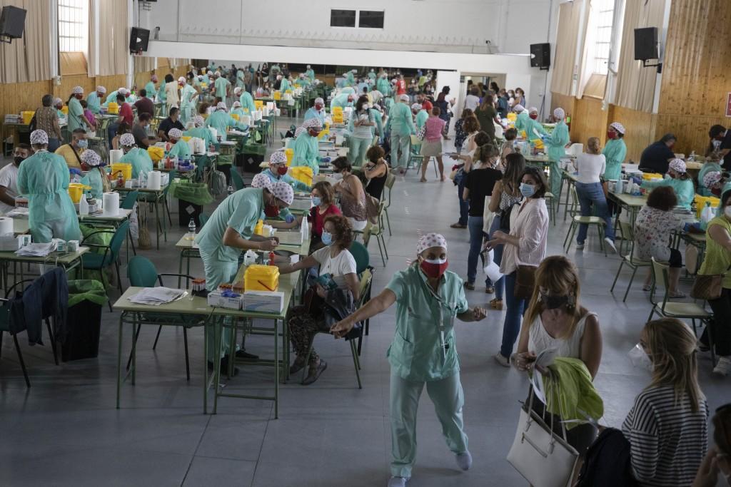 圖為西班牙一學校教師集體接受篩檢畫面。(美聯社圖片)
