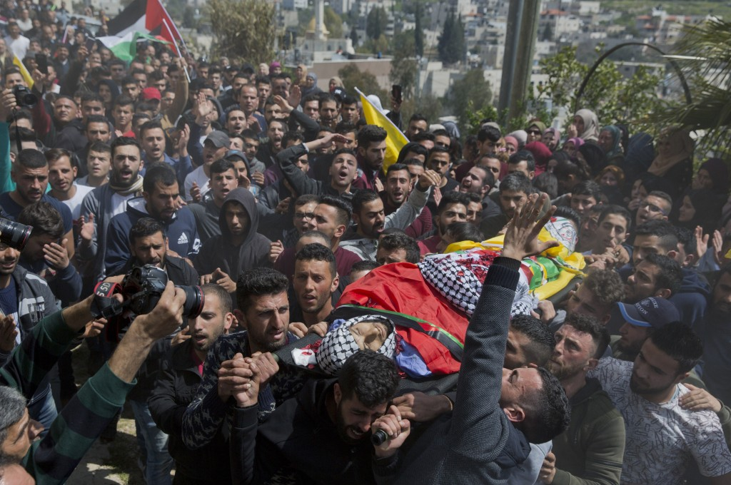 FILE - In this March 21, 2019 file photo, Palestinian mourners carry the body of Ahmad Manasra, during his funeral in the West Bank village of Wad Fok...