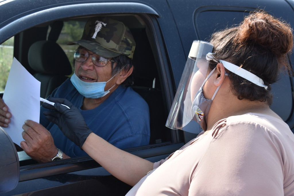 Selena Rides Horse speaks with Gerald Pease at a drive-thru station set up by Western Native Voice to help members of the Crow Indian Tribe participat...