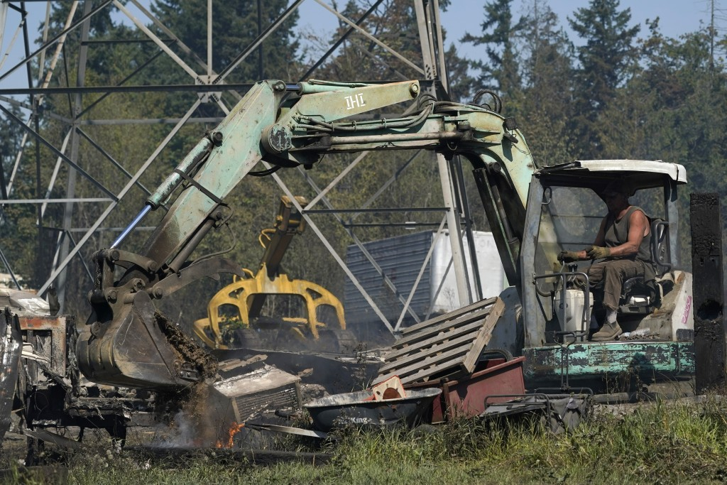 A person uses heavy equipment to put dirt on fire hotspots, Tuesday, Sept. 8, 2020, after a wildfire destroyed homes and outbuildings in Graham, Wash....
