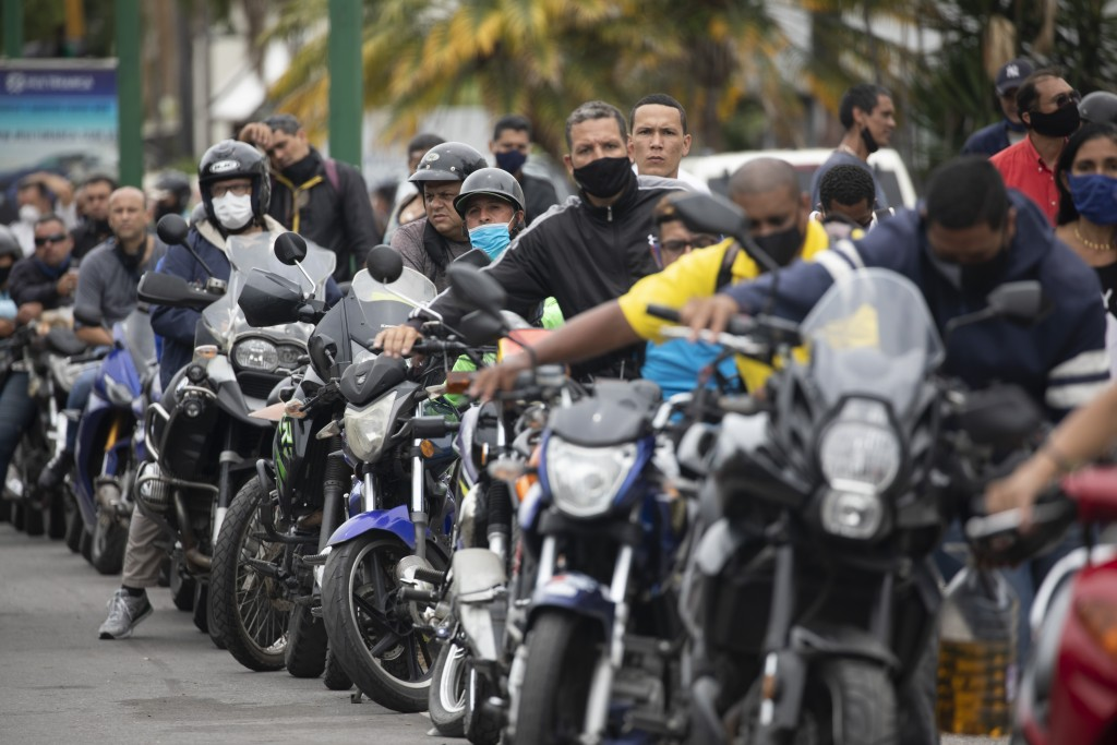 Motorcyclists wearing masks amid the new coronavirus pandemic wait their turn to fill up at a gas station in Caracas, Venezuela, Tuesday, Sept 8, 2020...