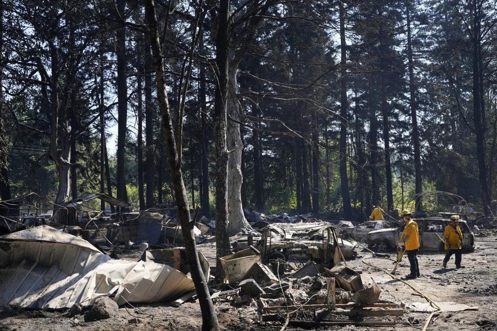 Firefighters work to put out hotspots, Tuesday, Sept. 8, 2020, after a wildfire destroyed homes and outbuildings in Graham, Wash., overnight south of ...