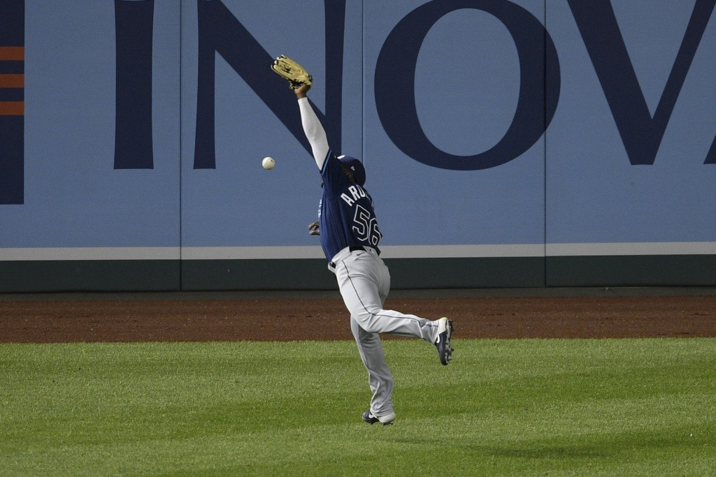 Tampa Bay Rays left fielder Randy Arozarena reaches for the ball on a double by Washington Nationals' Adam Eaton during the eighth inning of a basebal...