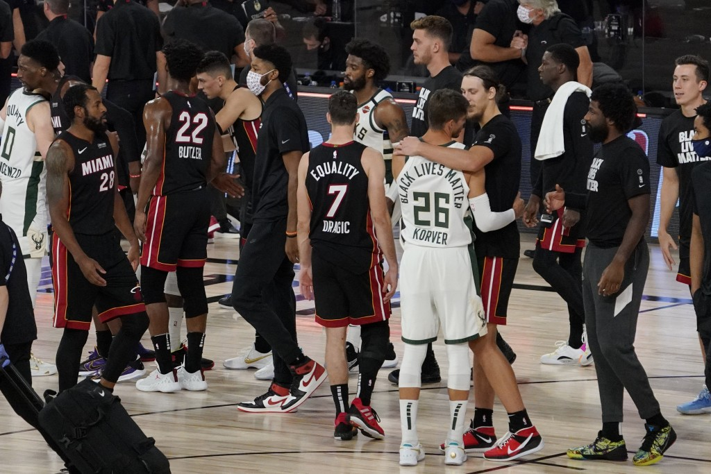 Miami Heat's Kelly Olynyk, right, and Milwaukee Bucks' Kyle Korver (26) embrace following their NBA conference semifinal playoff basketball game Tuesd...
