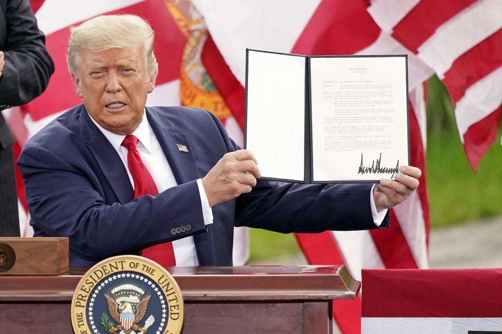 President Donald Trump holds a signed memorandum to expand the offshore drilling moratorium to Florida's Atlantic coast, Georgia and South Carolina af...