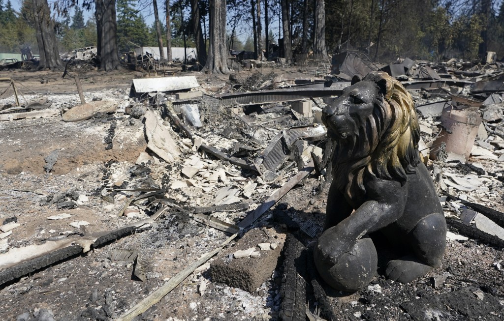 A decorate lion sculpture is shown charred by fire, Tuesday, Sept. 8, 2020, after a wildfire destroyed homes and outbuildings in Graham, Wash., overni...