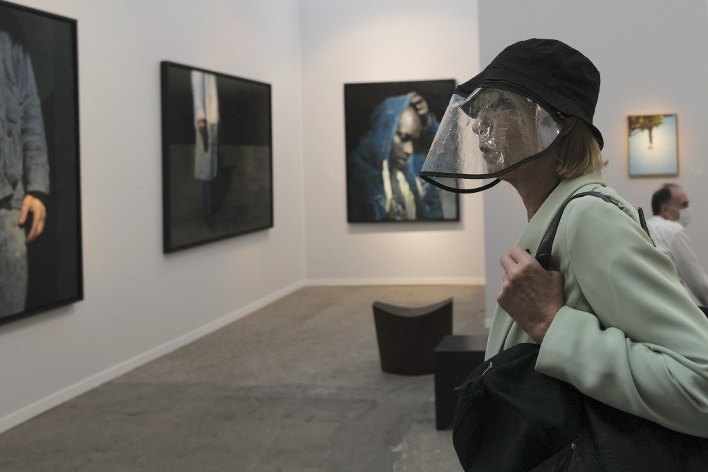 A visitor, wearing a protective face mask as a precaution against the coronavirus, looks on during the private view of Art Paris at the Grand Palais i...