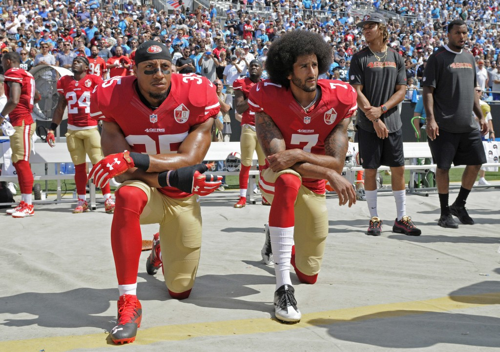 FILE - In this Sept. 18, 2016, file photo, San Francisco 49ers' Colin Kaepernick (7) and Eric Reid (35) kneel during the national anthem before an NFL...