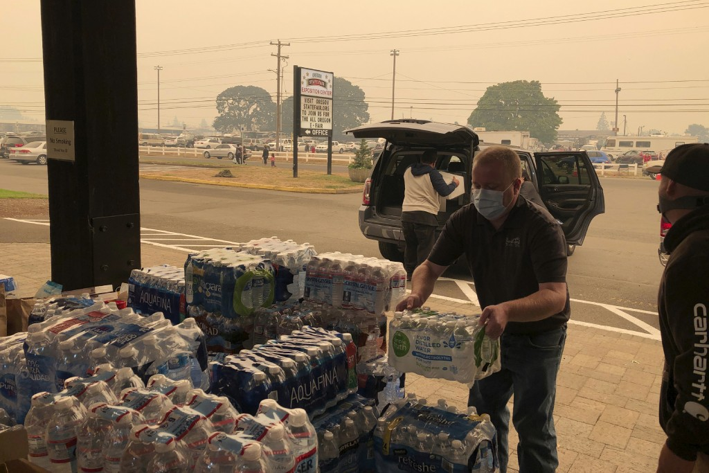 Jonathan Thompson of the Keizer, Oregon, Chamber of Commerce delivers donated bottled water on Tuesday, Sept. 8, 2020, to the Oregon State Fairgrounds...