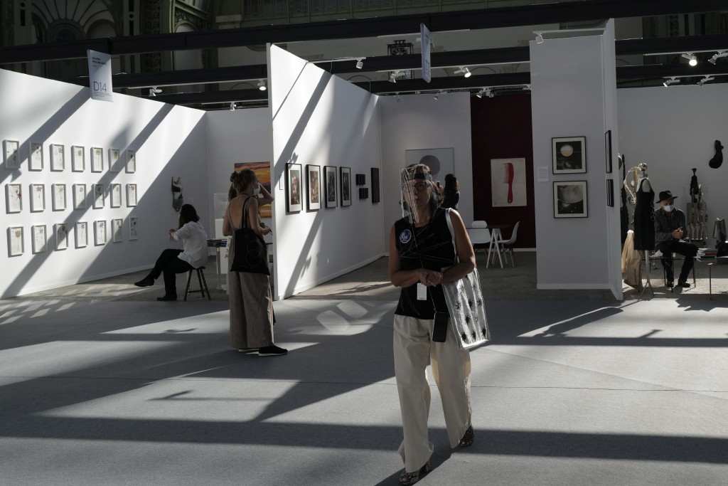 A visitor, wearing a protective face mask as a precaution against the coronavirus, looks on during the opening day of Art Paris at the Grand Palais in...