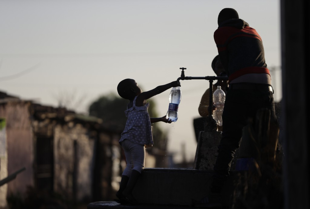 A child fills a bottle with water at a communal tap in the Katlehong Township near Johannesburg, Tuesday, Sept. 8, 2020. Official statistics show that...