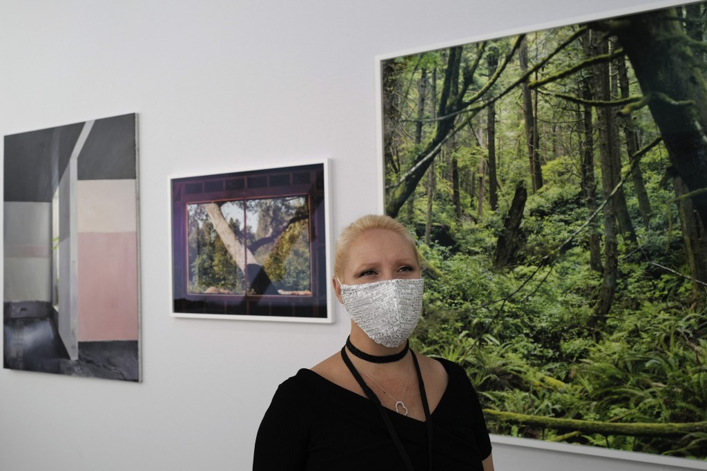 Heliante Bourdeaux-Maurin, H Gallery director, who is exhibiting at the fair, wears a protective face mask as a precaution against the coronavirus dur...