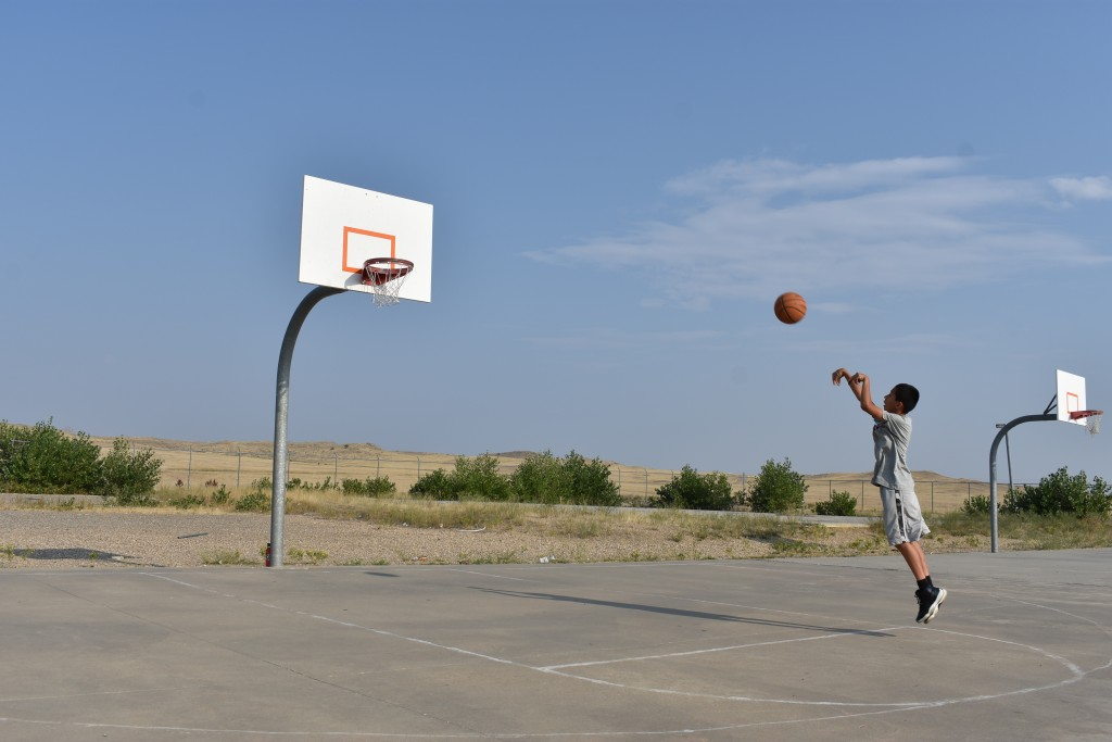 Julian Nomee, 14, shoots a basketball at a court on the Crow Indian Reservation near Crow Agency, Mont. on Wednesday, Aug. 26, 2020. U.S. Census offic...