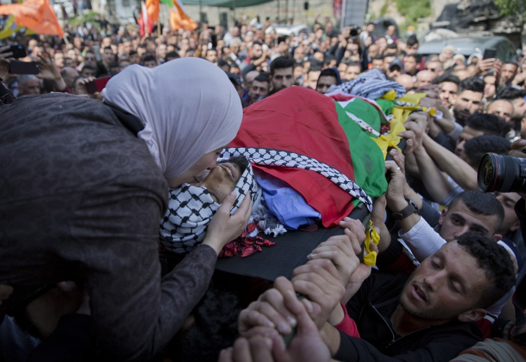 FILE - In this March 21, 2019 file photo, Wafa Manasra, mother of Palestinian Ahmad Manasra, kisses him goodbye during his funeral in the West Bank vi...